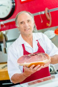Butcher holding joint of ham