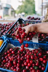 Crop person buying cherry