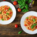 Penne pasta in tomato sauce with chicken, tomatoes, decorated with basil on a wooden table.