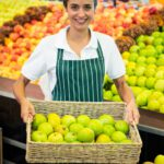 Smiling female staff holding a basket of green apple at supermarket