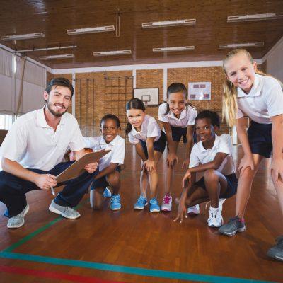 Portrait of sports teacher and school kids in basketball court